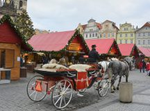 Prague, Czech Republic - December 2, 2015: Unidentified people on Christmas market on old town square and traditional horse drawn coach