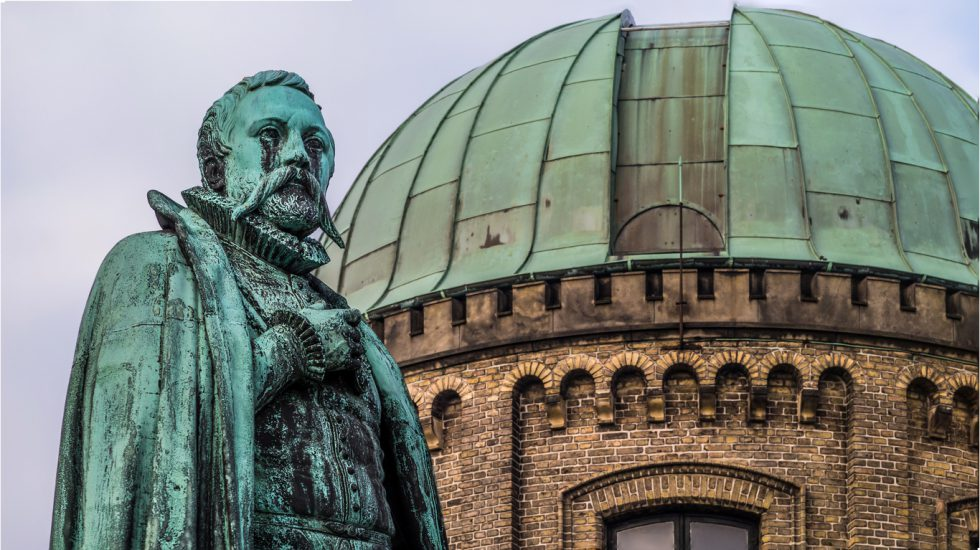 Statue of Tycho brahe in front of a green copper roofed observatory  next to Rosenborg castle in Copenhagen,  Denmark